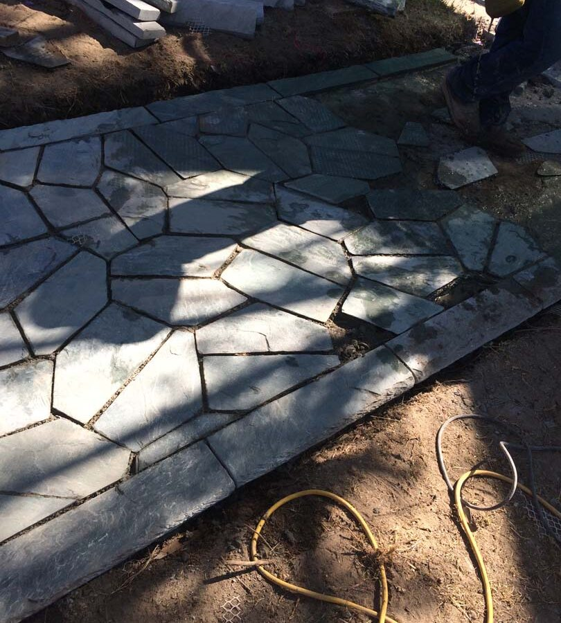 Construction of flagstone walkway. Each piece was hand cut and fixed in place. Pacificland Constructors