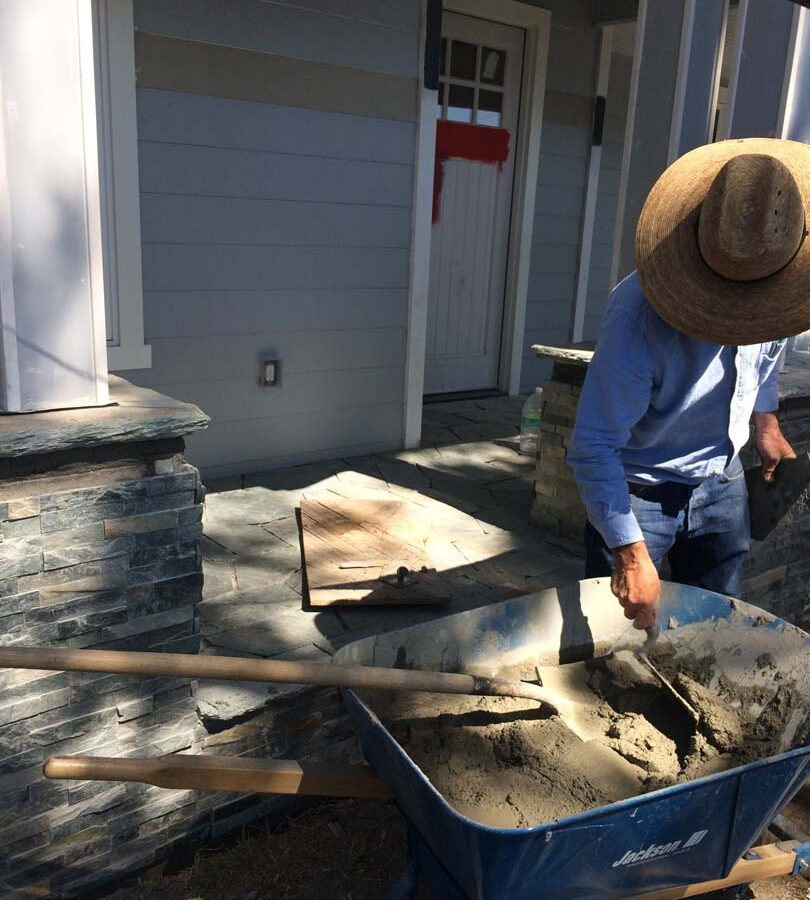 Martin, founder of Pacificland, installing a new flagstone walkway for a home's front yard's porch landing. Flagstone work is a great option to raise the value of your home. Pacificland Constructors