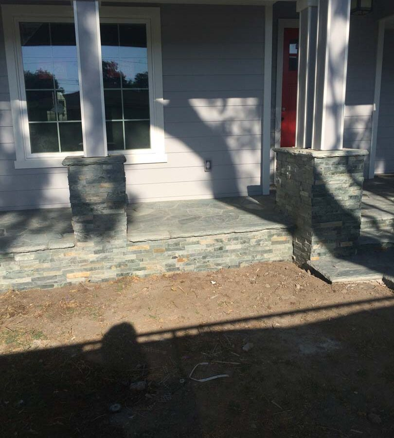 Flagstone flatwork at the entrance of a home. Artificial stone covered pilasters to create a modern theme. Pacificland Constructors