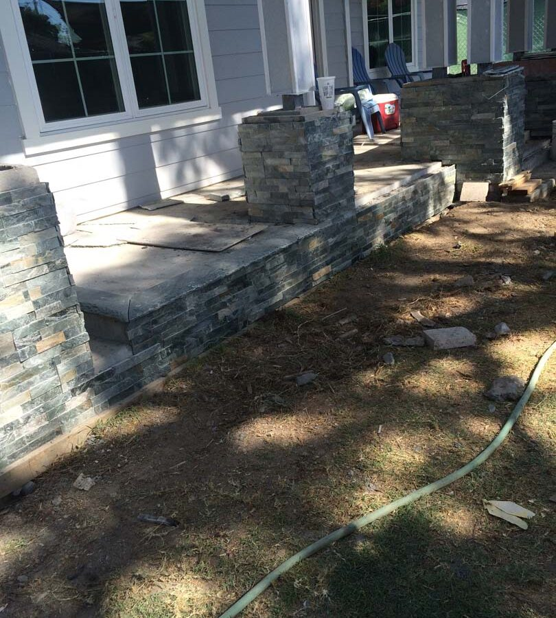 Construction of Flagstone flatwork at the entrance of a home. Artificial stone covered pilasters are intended to create a modern theme. Pacificland Constructors