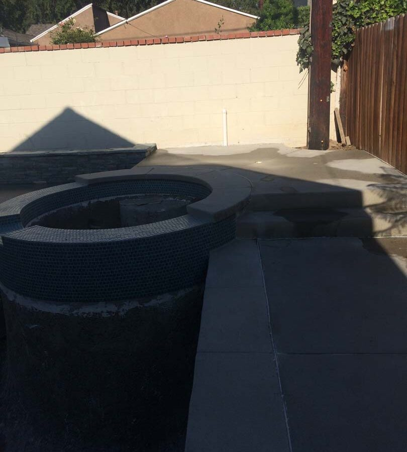 New gray concrete deck with a stone veneered planter with custom colored wall cap. Pacificland Constructors