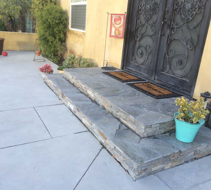New concrete backyard patio with beautiful flagstone covered concrete steps with stone veneer and a new artisan door. Pacificland Constructors