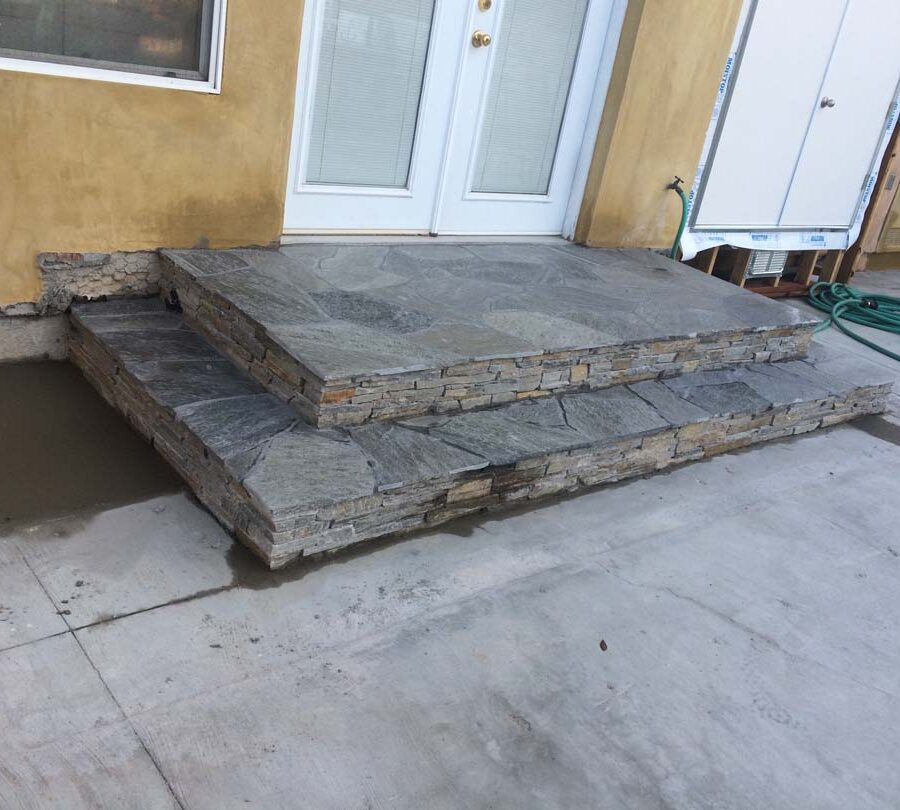 New stone veneer on the face of new concrete steps under an old door that will be replaced. Pacificland Constructors