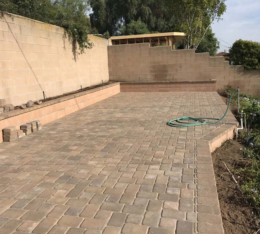 Finished paver patio with a CMU block planter. Pacificland Constructors