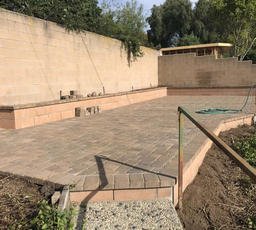 Finished paver patio with a CMU block planter. Pacificland Constructors.