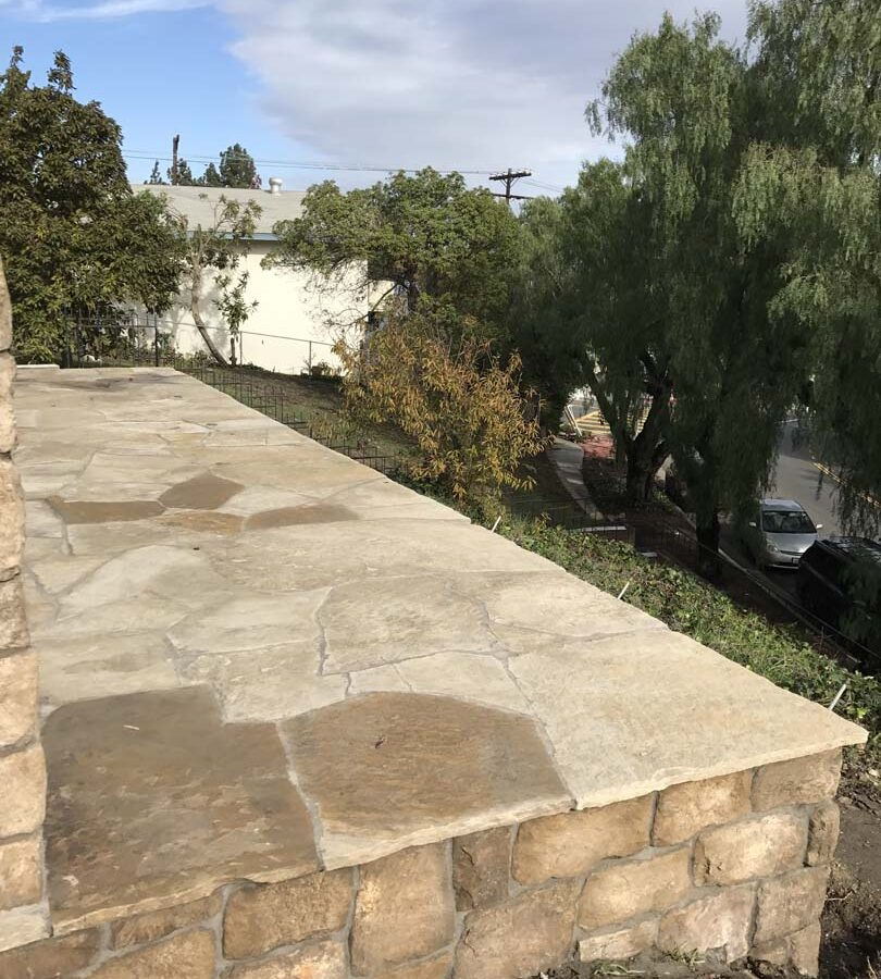 Stone veneer walls that match flagstone flatwork. Pacificland Constructors