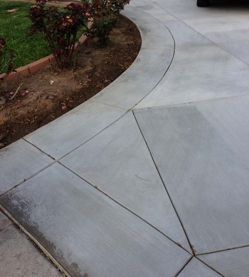 New gray concrete with diamond pattern and a ribbon around the perimeter. Surface is broom swept and has hand scorched joints. Pacificland Constructors