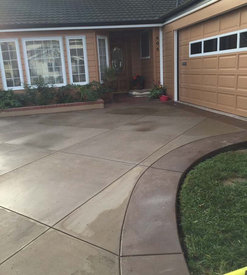 New colored concrete driveway with diamond pattern and a contrasting ribbon around the perimeter. The surface is broom swept and has hand scorched joints. Pacificland Constructors
